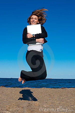 Happy business woman jumping with laptop