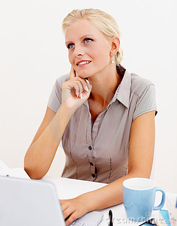 Happy business woman lost in thought while at work