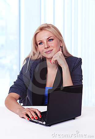 Happy business woman at office desk daydreaming