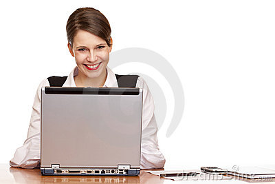 Happy business woman in office works on laptop