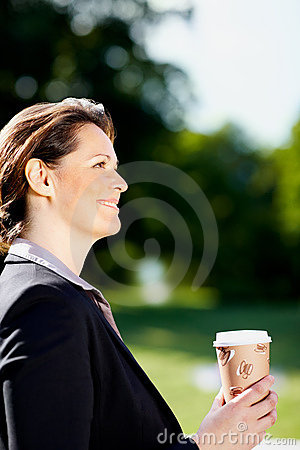 Happy business woman with a takeaway coffee