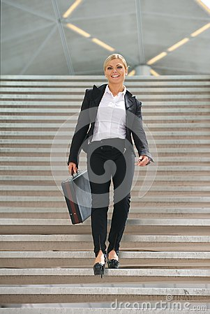 Happy business woman walking downstairs with briefcase