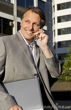 Happy businessman on cellphone.
