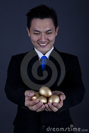 Happy businessman with golden eggs