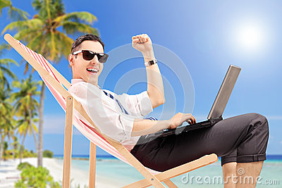 Happy businessman with a laptop on a beach