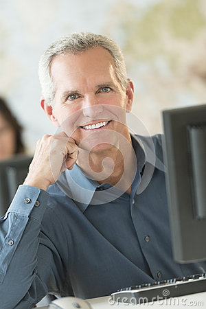 Happy Businessman Leaning At Computer Desk