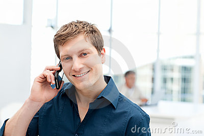 Happy businessman phoning in his office