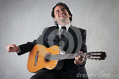 Happy businessman playing the guitar