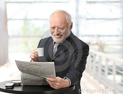 Happy businessman reading newspaper