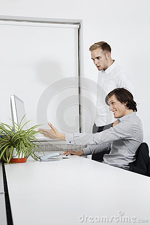 Happy businessman showing computer screen to coworker at desk
