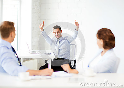 Happy businessman showing thumbs up in office
