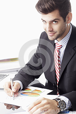 Happy businessman sitting in front of laptop
