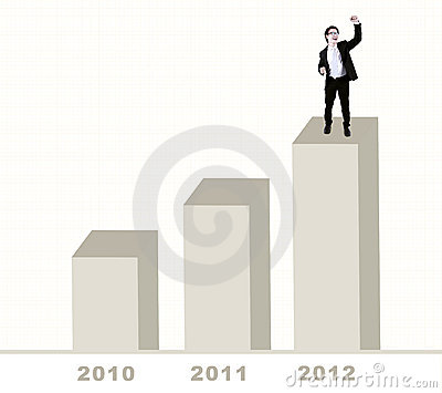Happy businessman standing on bar chart