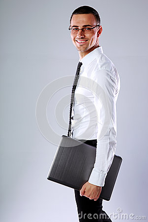 Happy businessman standing with laptop Stock Photo