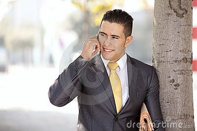 Happy businessman talking at his cellphone