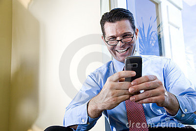 Happy businessman texting on mobile phone