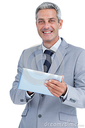 Happy businessman using tablet pc looking at camera