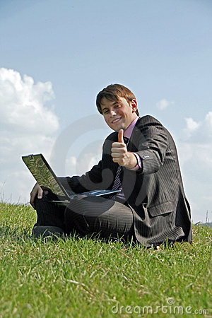 Happy businessman working with a laptop outdoor