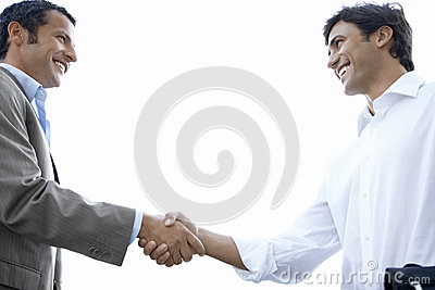 Happy Businessmen Shaking Hands Against Clear Sky
