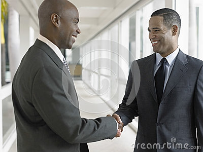 Happy Businessmen Shaking Hands In Office Corridor