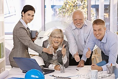 Happy businessteam giving thumbs up at work