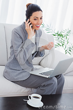 Happy businesswoman calling with her mobile phone and using laptop sitting on sofa