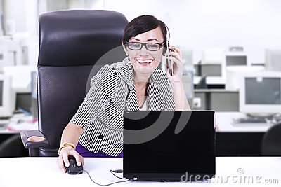 Happy businesswoman chatting on phone at office
