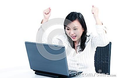 Happy businesswoman cheering in front of laptop