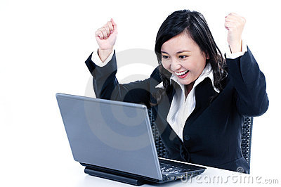 Happy businesswoman cheering in front of laptop