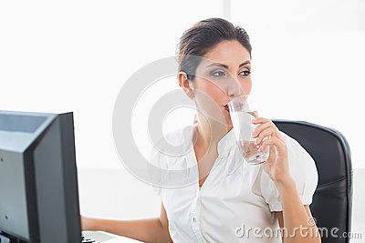 Happy businesswoman drinking a glass of water at her desk