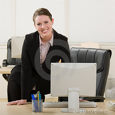 Happy businesswoman leaning on desk