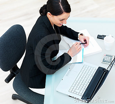 Happy businesswoman looking at laptop