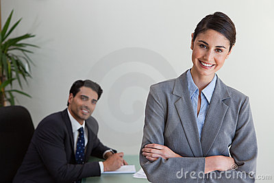 Happy businesswoman posing while her colleague is working