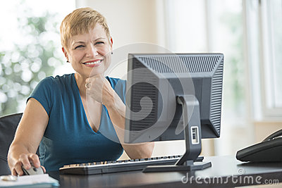 Happy Businesswoman Sitting At Computer Desk