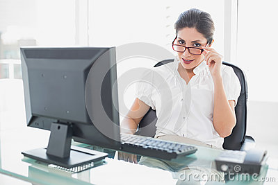 Happy businesswoman sitting at her desk looking at camera
