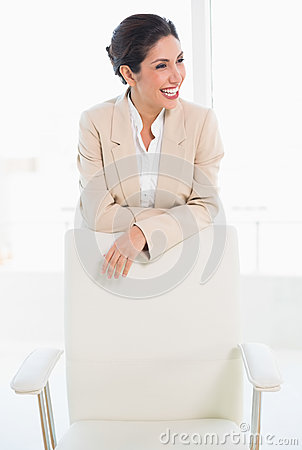 Happy businesswoman standing behind her chair