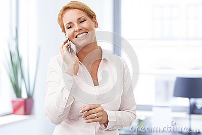 Happy businesswoman talking on mobile phone
