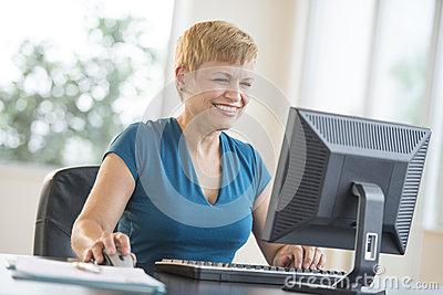 Happy Businesswoman Using Computer At Desk