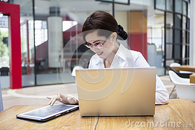 Happy businesswoman using tablet and laptop in cafe