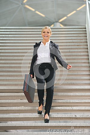 Happy businesswoman walking downstairs with briefcase