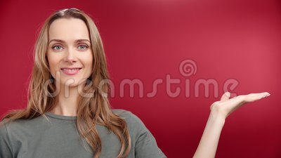 Happy casual European female model showing arm advertising area isolated at studio backdrop closeup. Pretty lady enjoying presenting commercial empty place stock video footage
