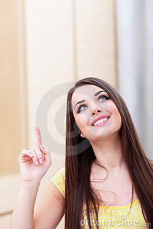 Happy casual woman pointing up