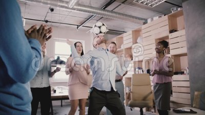 Happy Caucasian manager juggles football on head. Cheerful multiethnic employees celebrate success in office slow motion. Healthy lifestyle at workplace in stock video footage