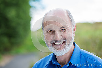 Happy Caucasian retired bearded man, outdoors