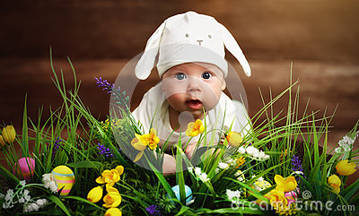 Happy child baby dressed as the Easter bunny rabbit on the grass Stock Photo