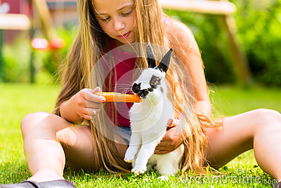 Happy child with bunny pet at home in garden