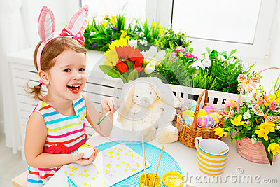 Happy child girl paints eggs for Easter Stock Photo