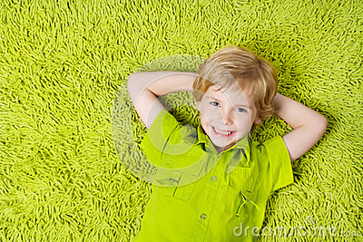 Happy child lying on the green carpet background