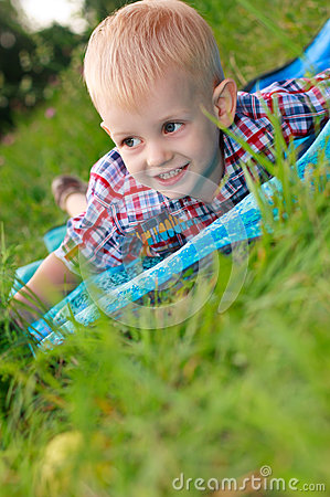 Happy child lying is among the green grass