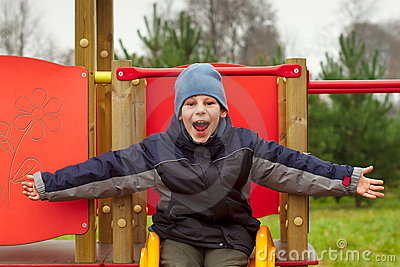 Happy child open arms screaming of joy playground